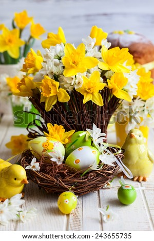 Easter table decoration with fresh daffodils,chick and eggs - stock photo