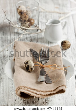 Easter table setting chicken and quail eggs on white wooden table - stock photo
