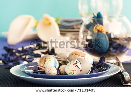 Easter table setting in blue and white tones with candles and flower. - stock photo