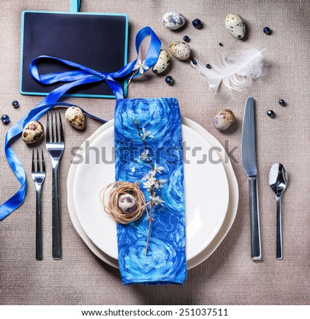 Easter table setting with blue textile napkin, blossom branch and quail eggs. Top view. - stock photo