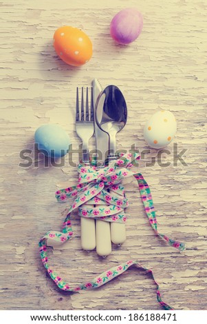 Easter table setting with colorful eggs on white wooden table - stock photo