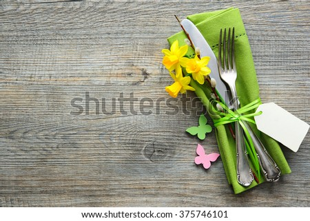 Easter table setting with daffodil and cutlery. Holidays background - stock photo