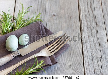 Easter table setting with eggs and rosemary - stock photo