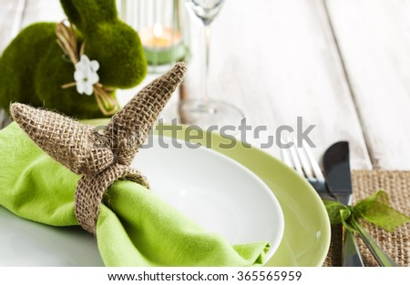 Easter table setting with green bunny decoration - stock photo