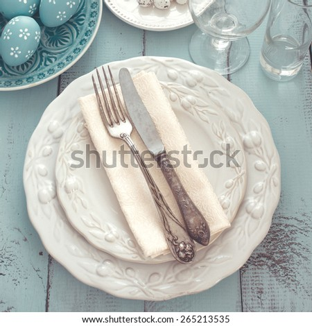 Easter table setting with holiday decor on mint wooden background, top view point - stock photo