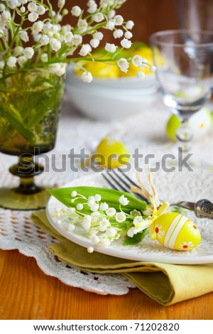 Easter table with  lily-of-the-valley and eggs - stock photo