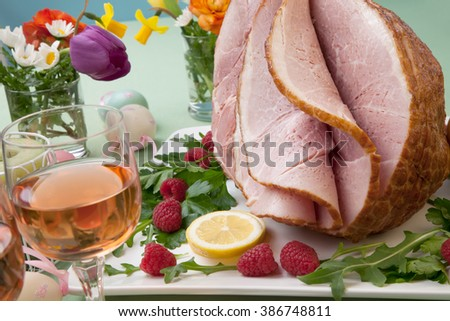 Easter themed prepared sliced honey ham and fresh raspberry, arugula, lemons, Ester eggs decoration. Spring flowers and pink wine.