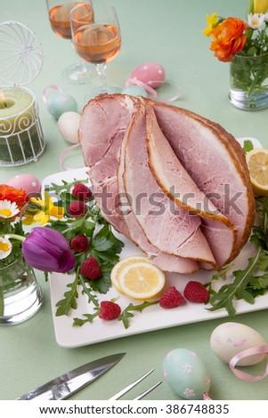 Easter themed prepared sliced honey ham and fresh raspberry, arugula, lemons, Ester eggs decoration. Spring flowers and pink wine. - stock photo