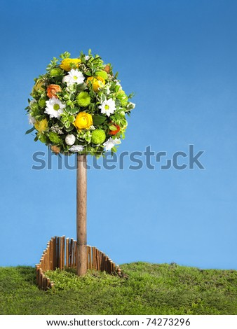 easter tree flower arrangement, blue sky and copy space - stock photo