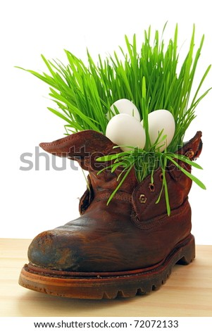 Easter white eggs in old shoes, with fresh grass - stock photo