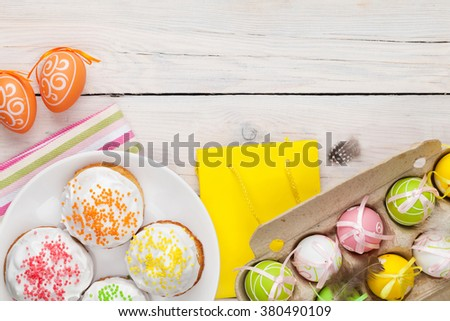 Easter with colorful eggs and traditional cakes over white wooden table. Top view with copy space - stock photo