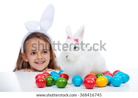 Easter with my bunny - little girl with white rabbit and colorful eggs, focus on the girl - stock photo