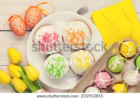 Easter with yellow tulips, colorful eggs and traditional cakes over white wooden table. Vintage toned - stock photo