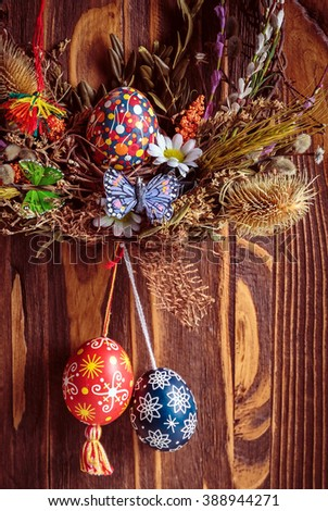Easter wreath with easter eggs, decorative butterflies, flowers and blooming willow on the wooden background. easter decorations. Happy Easter - stock photo
