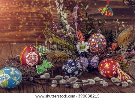 Easter wreath with easter eggs, decorative butterfly, flowers and blooming willow on the wooden background. easter decoration. happy easter. soft light toning effect - stock photo