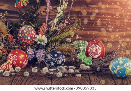 Easter wreath with easter eggs, decorative butterfly, flowers and blooming willow on the wooden background. easter decoration. happy easter. instagram and soft light effect - stock photo