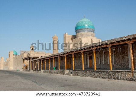 Eastern architecture. Bukhara. Street in the city of Bukhara in Uzbekistan. In the background a mosque with a blue dome in the foreground the shopping rows near the road.