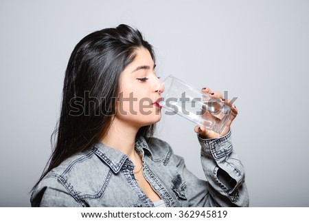 Eastern brunette girl drinks water from a glass, hipster denim clothing, photo studio, portrait emotions - stock photo