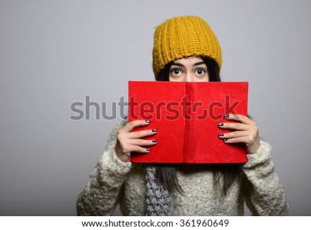 Eastern brunette girl hiding behind the book, hipster in winter clothing, photo studio, portrait of a woman isolated on gray background - stock photo