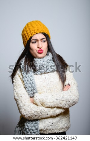 Eastern brunette girl looks with distaste, hipster in winter clothes, a photo studio, portrait emotions