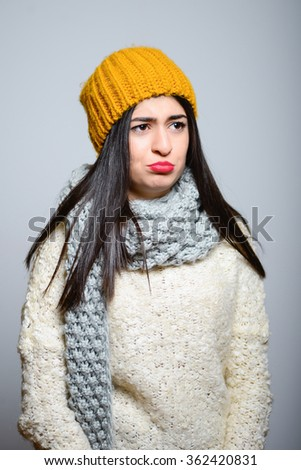 Eastern brunette girl offended hipster in winter clothing, photo studio, portrait of a woman isolated on gray background