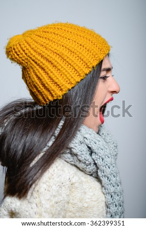 Eastern brunette girl shouting angry, hipster in winter clothes, a photo studio, portrait emotions