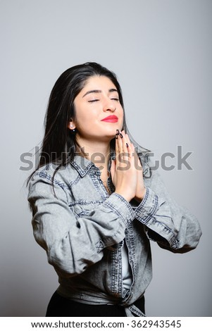 Eastern brunette woman folded her hands and prays, hipster denim clothes, isolated studio portrait emotions - stock photo