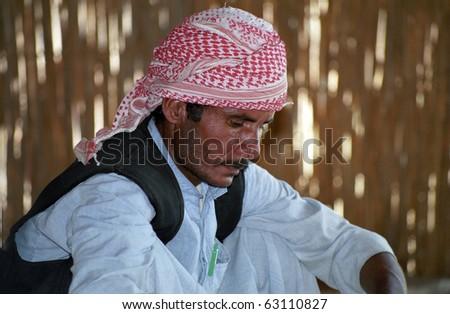 EASTERN DESERT, EGYPT - NOVEMBER 22 : Bedouin man prepares food in the village on November 22, 1998 in Eastern Desert, Egypt. Bedouins live in harsh conditions in the desert. - stock photo
