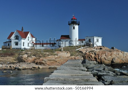 Eastern Point Lighthouse and breakwater, Gloucester, MA, on a clear spring day - stock photo