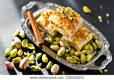 eastern traditional dessert with nuts and pistachios with a stick of cinnamon selective focus - stock photo