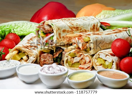 Eastern traditional shawarma plate with sauce. - stock photo