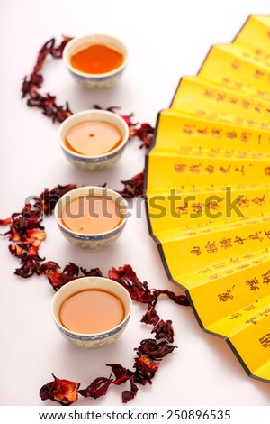 Eastern traditions. Top view image of crockery teacups surrounded by flower tea composition and Chinese hand fan isolated on white background with selective focus - stock photo