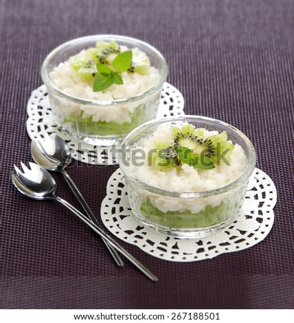 Easy healthy breakfast rice with kiwi in glass bowls on a purple background - stock photo