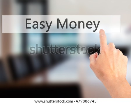 Easy Money - Hand pressing a button on blurred background concept . Business, technology, internet concept. Stock Photo