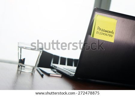 easy password on sticky note on back Laptop in office room as concept  - stock photo