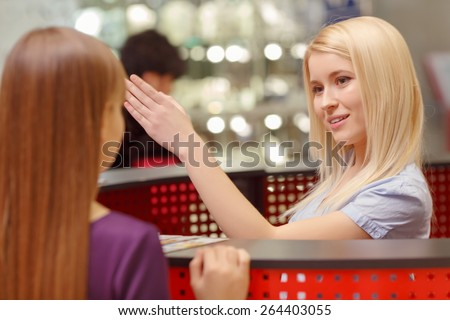 Easy shopping. Close-up of a pretty blond receptionist of the information desk in shopping mall showing the way to the customer  - stock photo