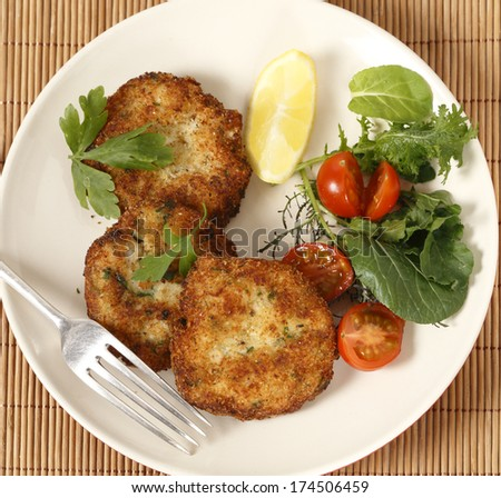 Easy to make fishcakes, with steamed fish crumbled into mashed potato and parsley mix, thickened with some flour, rolled in breadcrumbs and fried, served with a salad. High angle view - stock photo