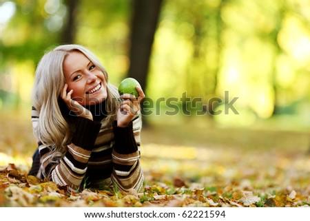 eat apple in autumn park - stock photo