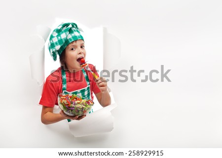 Eat fresh produce advertising - happy healthy young chef tasting vegetable salad - stock photo