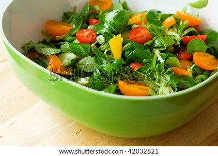 Eat healthy! Fresh vegetable salad served in a green salad bowl - stock photo