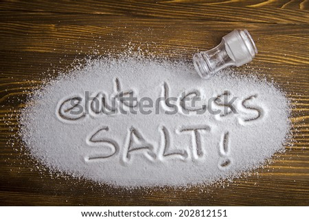 Eat less salt written on a heap of salt - anti-hypertensive campaign - stock photo
