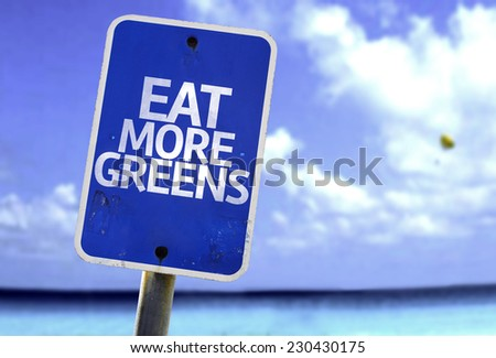 Eat More Greens sign with a beach on background - stock photo