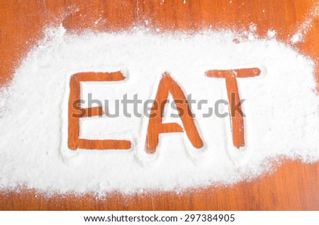 Eat sign with flour Artwork With Food And Handprints, Fun background with human handpints in scattered flour on a wooden tabletop.