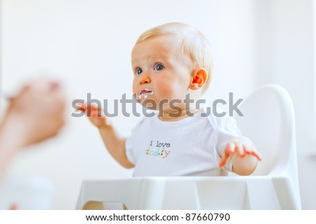 Eat smeared lovely baby girl in baby chair feeding by mother - stock photo