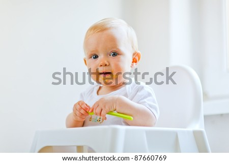 Eat smeared lovely baby girl with spoon in hand - stock photo