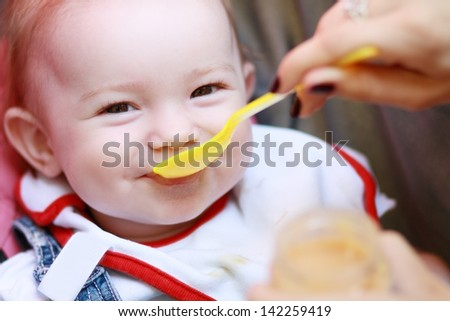 Eat smeared pretty baby girl eating from spoon outdoor - stock photo