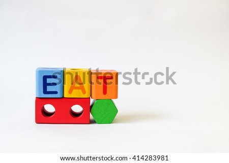 EAT word written on wood blocks, white background with copyspace - stock photo