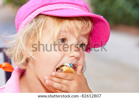 Eating a delicious cookie with cream frosting. - stock photo