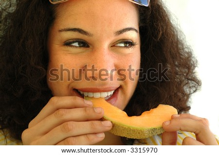 Eating a juicy cantaloupe with a smile - stock photo