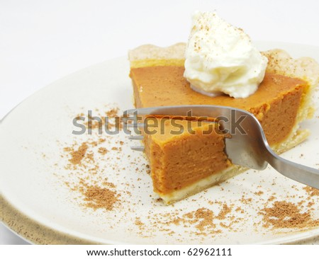 Eating a slice of pumpkin pie with whipped cream.